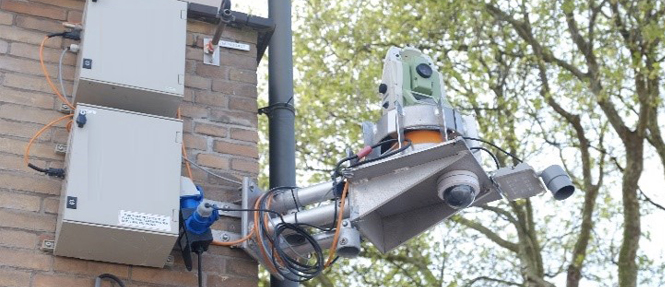Robotic total station mounted on a building